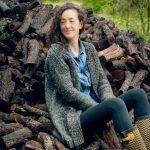 foto elia sentada junto a troncos sonriendo